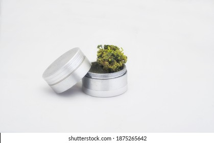 A recreational sativa strain of marijuana flower bud in a stainless steel metal grinder closeup on a white background.
