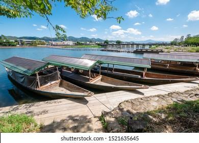 Recreational traditional japanese wooden boats, Katsura River and togetsuokyo bridge in Arashiyama village Japan