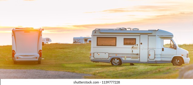 Recreational vehicle at sunset in Norway, Europe. Meadow with cloudy sky and sun. Travel by RV. Nordic country, Europe, Scandinavia.