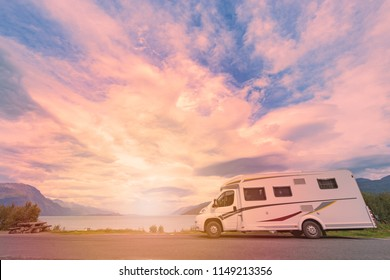 Recreational vehicle at sunset in Norway, Europe. Meadow and coast with cloudy sky and sun. Travel by RV. Nordic country, Europe, Scandinavia.