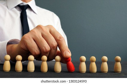 Recruiter choosing one figurine from the crowd. Talent management and hiring.