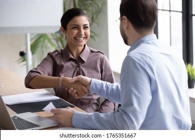 Recruiter shaking successful smiling Indian businesswoman candidate hand at meeting, congratulating with getting new job, manager making great deal with customer, diverse business partners greeting