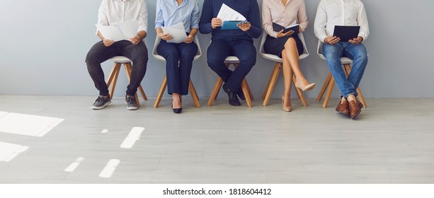 Recruitment process and office paperwork concepts. Low section crop of group of job candidates waiting in line for interview. Company workers with documents sitting in queue on chairs