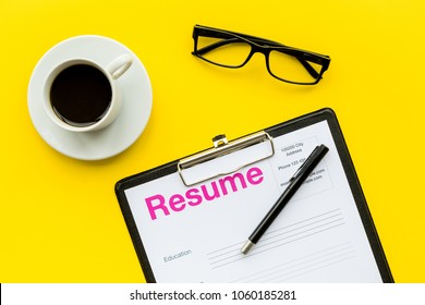 Recruitment. Select employees. Resume near coffee, glasses on yellow background top view