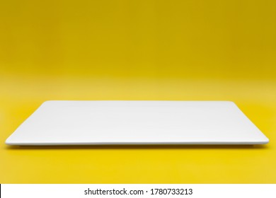 A rectangle empty white plate isolated on the yellow background.