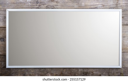 Rectangle picture frame laid on wooden floor background.