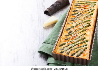 Rectangle-shaped grilled asparagus savory tart with pecorino and bacon next to a french cutting knife on a rustic wooden background. With copy space.