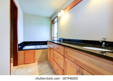 Rectangular bathroom with window. View of cabinets with black counter top and white bathroom with black tile trim