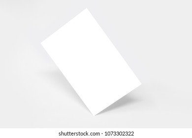 Rectangular blank card standing on its angle, with shadows, isolated on a white background
