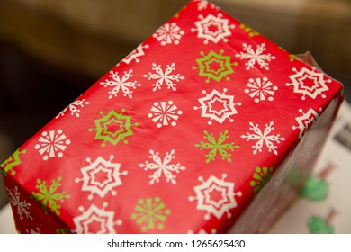 Rectangular box wrapped in red, white, and green wrapping paper.