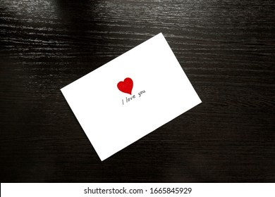 Rectangular envelope with a heart on the wooden table top. Love letter. Making a gift for an apology, Declaration of love, pleasant to your girlfriend, wife on Valentine's Day, wedding, birthday.