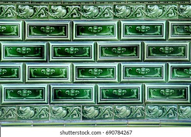 Rectangular green tiles on the facade of a traditional chinese peranakan shophouse. Tiles have an embossed floral pattern and are bordered at the top and bottom with a continuous patterned edging tile