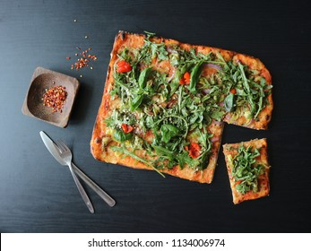 Rectangular pizza, square pizza on dark wooden background. Pizza with rocket leaves and chili flakes on black background. Pizza slice on wood.