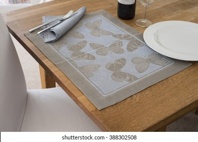 A rectangular placemat with embroidered butterflies as design spread out on wooden table with napkin and utensils atop alongside empty dinner plate, wine glass, and a bottle of wine.