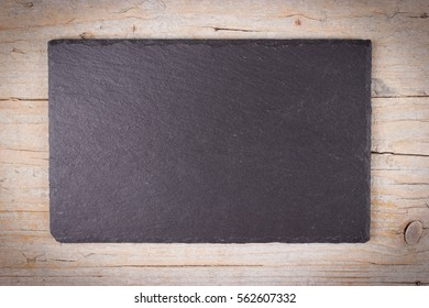 Rectangular plate made of black slate on wooden background. Top view with copy space.