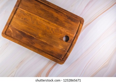 Rectangular shaped wood cutting board on dark concrete background. Top view with copy space for text.