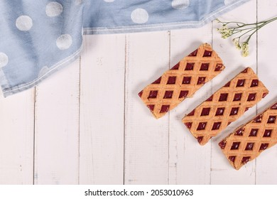 Rectangular slices of pie called 'Linzer Torte', a traditional Austrian shortcake pastry with fruit preserves and sliced nuts with lattice design on side of wooden table with copy space