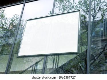 Rectangular white billboard Mockup on glass window. Empty frame on company building frontage