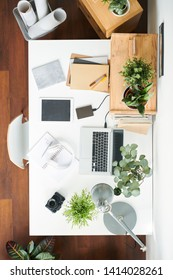 Rectangular white desk with modern mobile gadgets, green plants in flowerpots, copybooks, lamp and photocamera