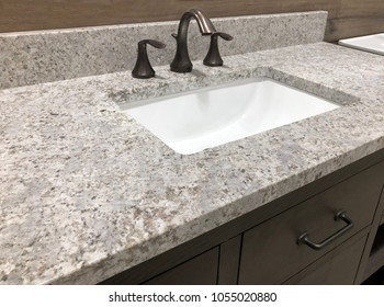 rectangular white sink under granite countertop and with brown wood vanity cabinet
