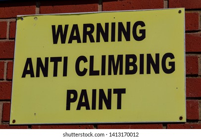 Rectangular yellow and black sign warning of anti climbing paint Widnes April 2019
