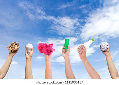 Recyclable hand hold show symbol plastic bottle used paper canned light bulb a sky background