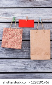 Recyclable paper bags hanging on rope with clothespins. Brown paper bags and note hanging on a rope attached with colorful wooden clothespin.
