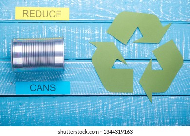 Recycle concept showing cans with the green recycle logo & reduce on a blue weathered background