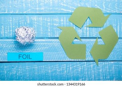 Recycle concept showing foil with the green recycle logo on a blue weathered background