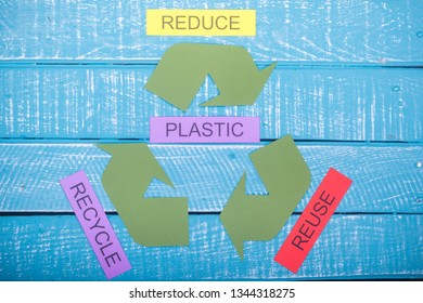 Recycle concept showing the green recycle logo with reduce,reuse,recycle & plastic on a blue weathered background