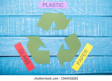 Recycle concept showing the green recycle logo with paper, plastic & glass on a blue weathered background