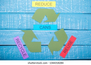 Recycle concept showing the green recycle logo with reduce,reuse,recycle & cans on a blue weathered background