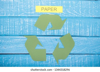 Recycle concept showing the green recycle logo with paper on a blue weathered background