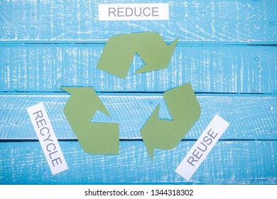 Recycle concept showing the green recycle logo with reduce, reuse, recycle on a blue weathered background