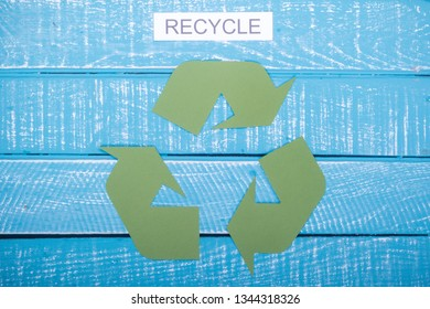 Recycle concept showing the green recycle logo with recycle on a blue weathered background