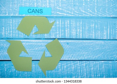 Recycle concept showing the green recycle logo with cans and copy space on a blue weathered background