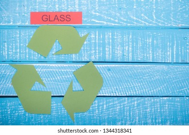 Recycle concept showing the green recycle logo with glass and copy space on a blue weathered background