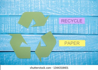 Recycle concept showing the green recycle logo with recycle paper on a blue weathered background