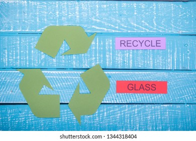Recycle concept showing the green recycle logo with recycle glass on a blue weathered background