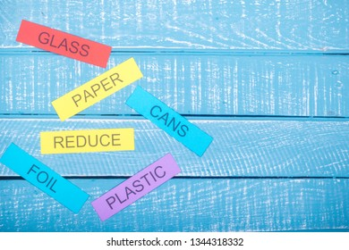 Recycle concept showing on waste items listed with reduce a blue weathered background with copy space