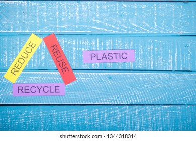 Recycle concept showing reduce, reuse & recycle on a blue weathered background with plastic