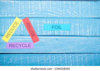 Recycle concept showing reduce, reuse & recycle on a blue weathered background with foil