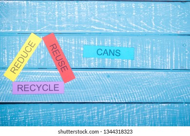 Recycle concept showing reduce, reuse & recycle on a blue weathered background with cans and copy space