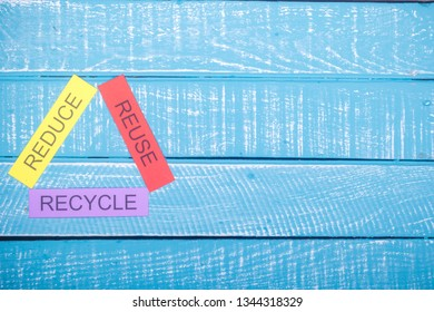 Recycle concept showing reduce, reuse & recycle on a blue weathered background with copy space