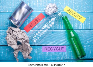 Recycle concept showing waste products of paper, glass, plastic, foil paper & reduce, recycle, reuse on a blue weathered background