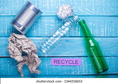 Recycle concept showing waste products of paper, glass, plastic, foil paper & recycle on a blue weathered background