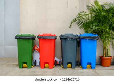 Recycle garbage bins or Sorted recycling bins in multiple color beside the building