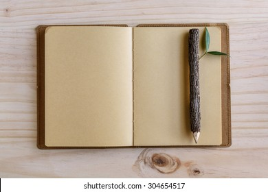 Recycle notebook with wooden pencil on wooden desk, conservation concept