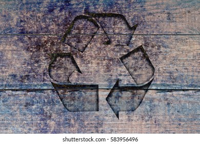 Recycle sign on a wood background