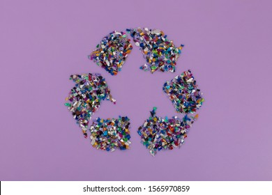 Recycle symbol consisting of small plastic pellets collected from the sea water. Rethinking the environment by reducing or reusing plastics. Circular economy concept. Lilac purple background